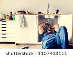 plumber man fixing kitchen sink | Shutterstock . vector #1107413111