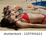 four sunbathing women in bikini ... | Shutterstock . vector #1107441611