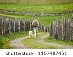tourist with dog in countryside.... | Shutterstock . vector #1107487451
