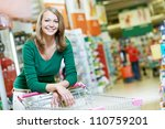 One happy women with shopping cart at supermarket shopping mall store - stock photo