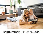 father with her baby and a book ... | Shutterstock . vector #1107763535