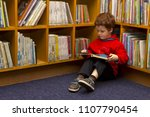 Boy Sitting In A Library...