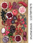 Small photo of Health food concept with vegetables and fruit high in anthocyanins, minerals, antioxidants and vitamins on rustic oak background. Foods in blue, red & purple colours denoting presence of anthocyanin.