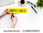 Small photo of Make the impossible possible. Cutting the part im of written word impossible by sciccors. Office desk. White background top view space for text