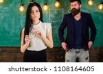 Small photo of Lady teacher and bearded hipster schoolmaster working together in school. Man with beard and young lady teacher stand in classroom, chalkboard on background. Generation concept.