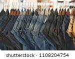 Many jeans hanging on a rack....