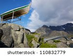 Bridge leading to town Henningsvaer on Lofoten islands with old fishing boat - stock photo