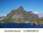 Picturesque town of Reine by the fjord on Lofoten islands in Norway with high mountain peaks towering above - stock photo
