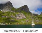 Fishing boat in fjord on Lofoten islands in Norway - stock photo