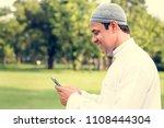 muslim man using smartphone | Shutterstock . vector #1108444304