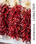 Small photo of Dried chile, chili wreath and ristras hanging in market in Santa Fe, New Mexico.
