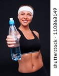 smiley sportswoman holding bottle of water over dark background - stock photo