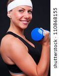 portrait of smiley sportswoman with blue dumbbells - stock photo