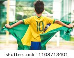 Stock photo brazilian boy holding the flag of brazil 1108713401