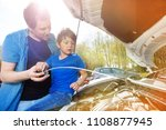 dad showing his son oil level... | Shutterstock . vector #1108877945