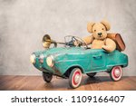 Stock photo teddy bear and old leather school bag driving in rusty retro turquoise toy pedal car with classic 1109166407