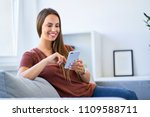 smiling young woman using phone ...   Shutterstock . vector #1109588711