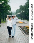 attractive couple in the rain...   Shutterstock . vector #1109608355