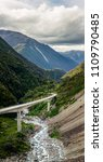 Small photo of Panoram of the Otira Highway in a valley of Arthurs Pass through the mountains of New Zealand's South Island on a cloudy summer day. A river flows beneath the highway between the tall mountains.