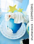 Small photo of Delicious birthday, christening or baby shower cake decorated with sleeping newbotn. Blue abd white colors for little boy party.