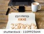 Small photo of Closeup on notebook over vintage desk surface, front focus on wooden blocks with letters making Estimated Tax text. Business concept image with office tools and coffee cup in background