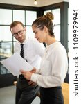 Small photo of Coworkers talking and discussing document. Business man standing and talking with female colleague with blurred office window in background. Colleagues concept.