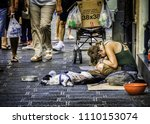 Small photo of 23 August 2014 - Sicily, Italy. Poor young homeless woman with the dog, sitting and begging for money in the busy street of coastal city of Catania located in Sicily, Italy.