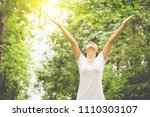 happy asian woman hands up... | Shutterstock . vector #1110303107