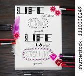 Small photo of Hand lettering - A motto about life, drawn by hand, in pink and red decoration elements