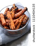 Small photo of Side dish of oven roasted carrots with black char marks, on a blue linen table cloth and space for text on top and bottom