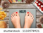 Stock photo feet of woman on weighting scale asking for help to avoid the temptation to eat unhealthy food 1110578921