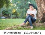 asian girl reading book at park ...   Shutterstock . vector #1110693641