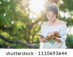 asian girl reading book at park ...   Shutterstock . vector #1110693644