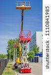Small photo of Yellow self propelled articulated boom lift and two red scissor lifts on background of building, trees and sky