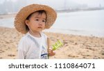 asian baby playing by the beach | Shutterstock . vector #1110864071