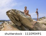 Mother and daughter on the rocky beach - stock photo