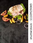 Small photo of Paninies or sandwiches with ham and egg abd potatoes on black wooden background