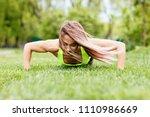 beautiful woman doing push ups... | Shutterstock . vector #1110986669