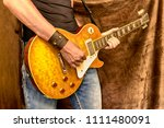 Small photo of Man (musician, guitarist, rock, metall player or bluesman, blues performer) plays electric guitar. Leather wristband or bracelet with metal skulls on hand and jeans, only hands with guitar close-up