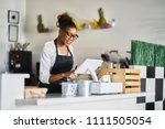 smiling shop assistant using... | Shutterstock . vector #1111505054