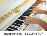 the hand of a child playing an... | Shutterstock . vector #1111545707