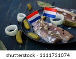 Stock photo traditional dutch food herring with pickled cornichons and onion on dark blue ceramic plate and 1111731074
