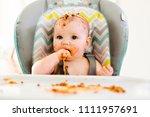 little baby eating her dinner... | Shutterstock . vector #1111957691