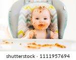 little baby eating her dinner... | Shutterstock . vector #1111957694