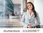 Small photo of Smiling likable sincere and charming business woman financial executive type portrait inside commercial building