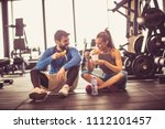 young couple at gym eating... | Shutterstock . vector #1112101457