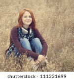 Young  smiling girl with headphones at field. - stock photo