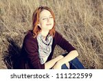 Portrait of happy red-haired girl on autumn grass. - stock photo