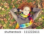 The red-haired girl in autumn leaves. Outdoor shot. - stock photo