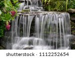 small waterfall in the garden. | Shutterstock . vector #1112252654